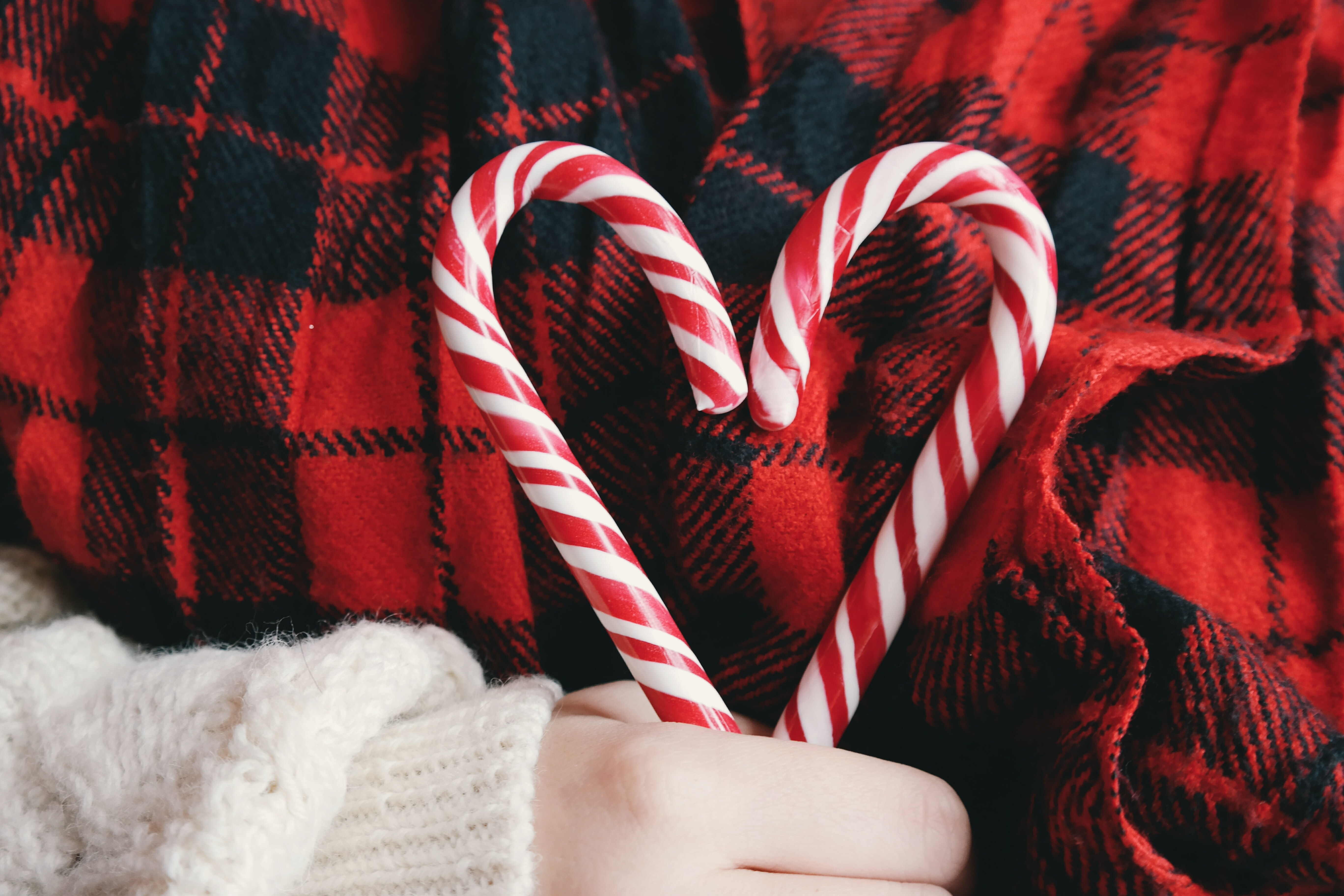person holding candy cane heart with red and black plaid background