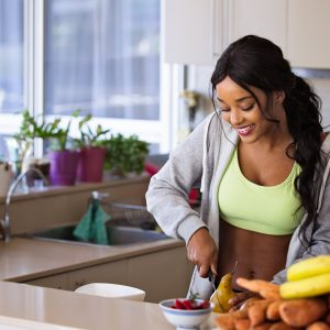 woman cutting up healthy foods in a kitchen